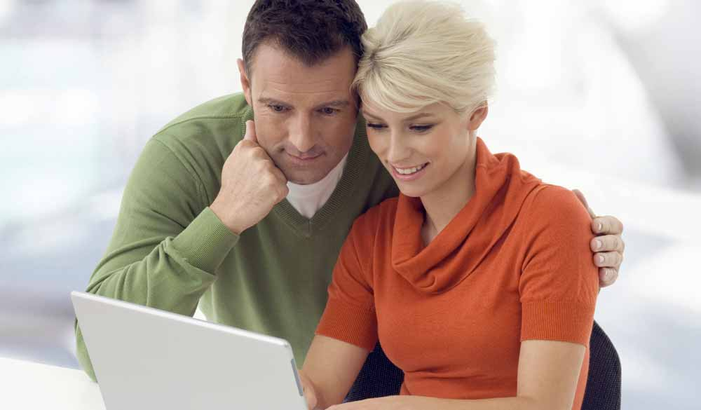 couple viewing a web design on a laptop